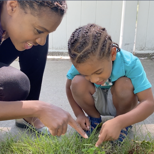 A boy and a Buildup coordinator pointing at grass