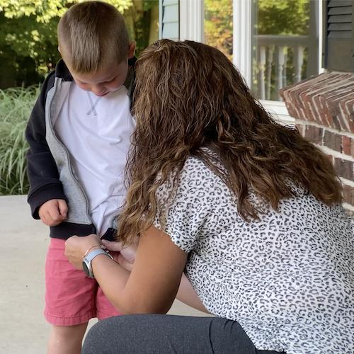 A BuildUp coordinator zipping a boy's zipper sweatshirt