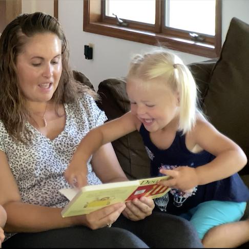 A BuildUp volunteer helping a girl read a book