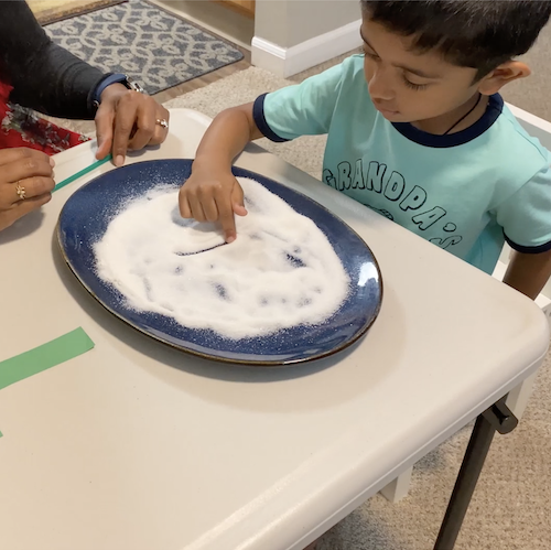 A boy putting his finger in a plate of white sand for special needs learning