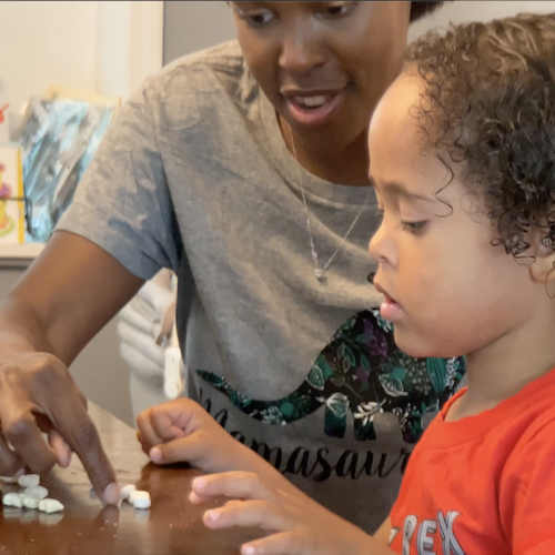 A special needs BuildUp coordinator helping a child with Maths by using small blocks