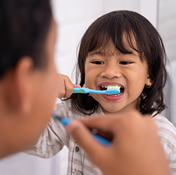 A girl child brushing her teeth looking at an adult doing the same