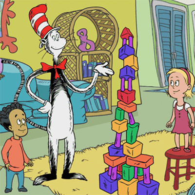 An animated scene with two children and a comic animal wearing a red and white hat looking at building blocks