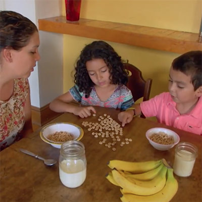 A boy and a girl playing with grains at the dining table and a Build Up coordinator helping them