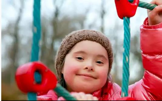 Young Girl with Down Syndrome Playing on a Playground
