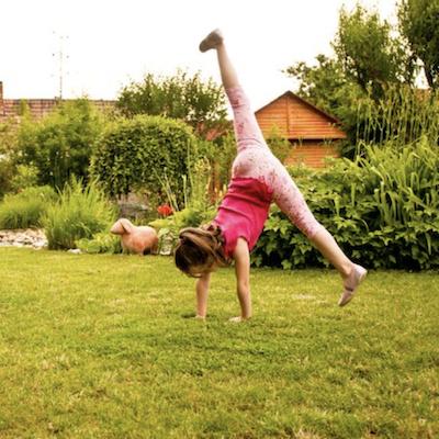 A Build Up special needs child cartwheeling in a garden