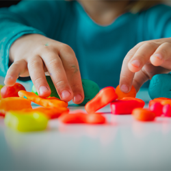 A special child's fingers picking up play toys on a table