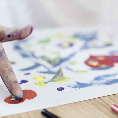 A special child's finger smudging red color on a paper indicating art therapy