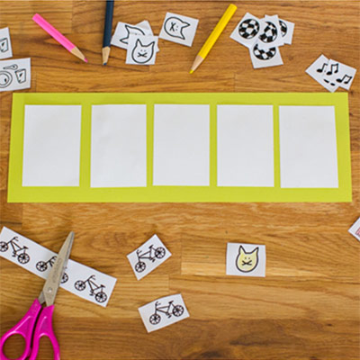 A fluorescent yellow paper with 5 white box-shaped papers pasted on it and stickers and a scissor scattered around for education