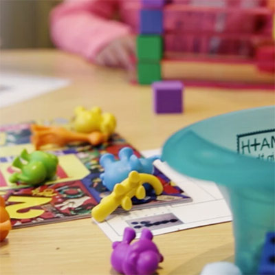 Play toys scattered around and a special child's hand in the background