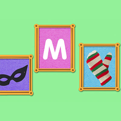Three photo frames containing an eye mask, the letter M and a striped red and green glove, one in each