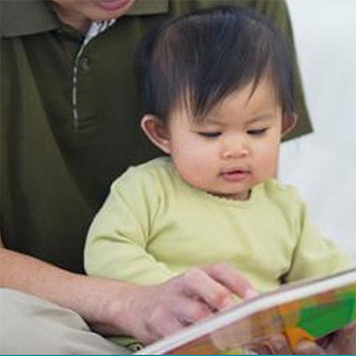 A child sitting on an adult's lap and reading a book