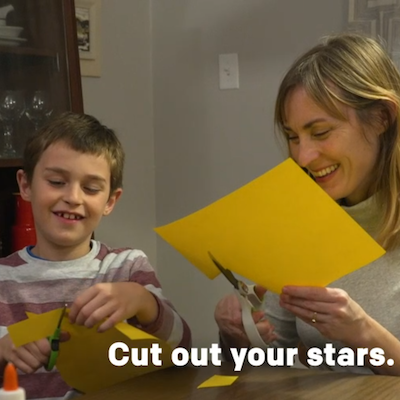 A special needs Build Up coordinator and a boy child cutting yellow papers with scissors