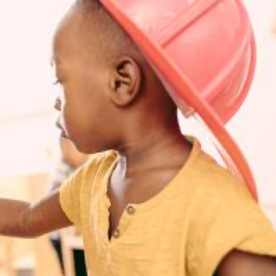 A child wearing a red hat looking sideways